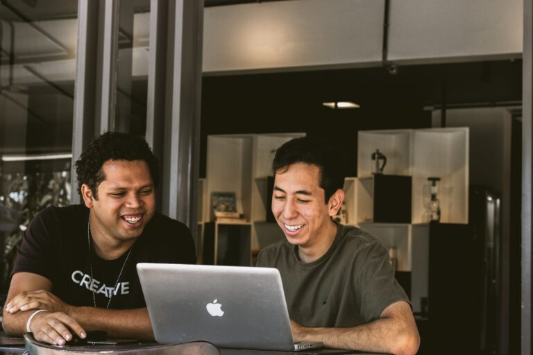 two smiling men looking at MacBook