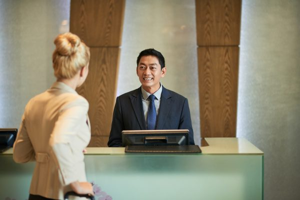 Business lady talking to receptionist of hotel