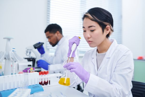 Concentrated young Asian female lab technician with short hair sitting at desk and dropping yellow liquid into flask while testing sample