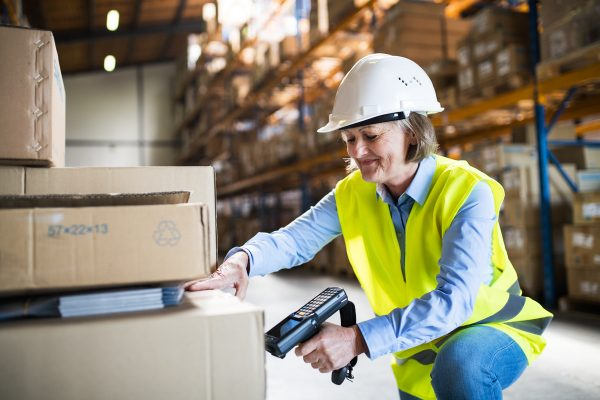 Senior warehouse woman worker or supervisor using a mobile handheld PC with barcode scanner.