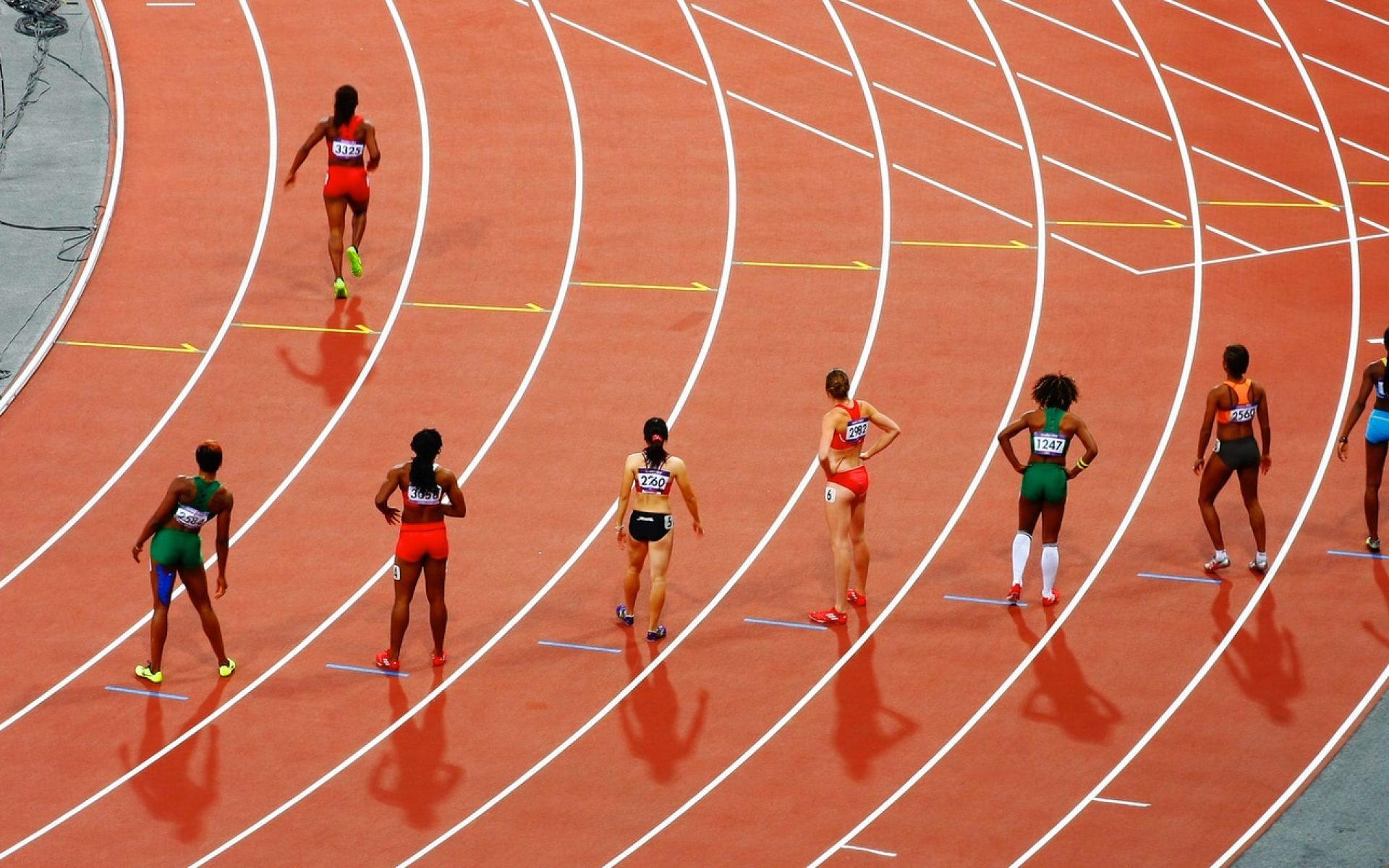 women running on race track during daytime